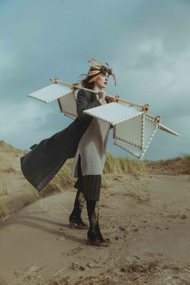 Icarus-editorial-woman-on-the-beach-conceptual-portrait-wooden-wings-in-windy-day-with-plastic-wrap-flying