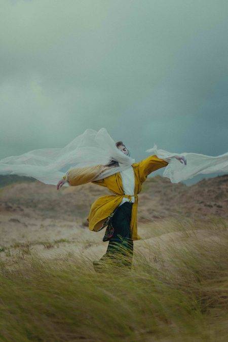 Icarus-editorial-woman-on-the-beach-conceptual-portrait-wooden-wings-in-windy-day-with-plastic-wrap-flying-with-yellow-coat