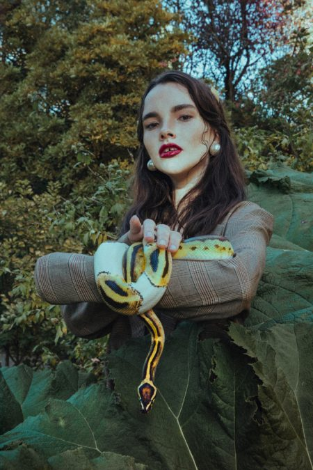 Photo of girl with square pattern blazer holding a snake on her arm next to big leaves