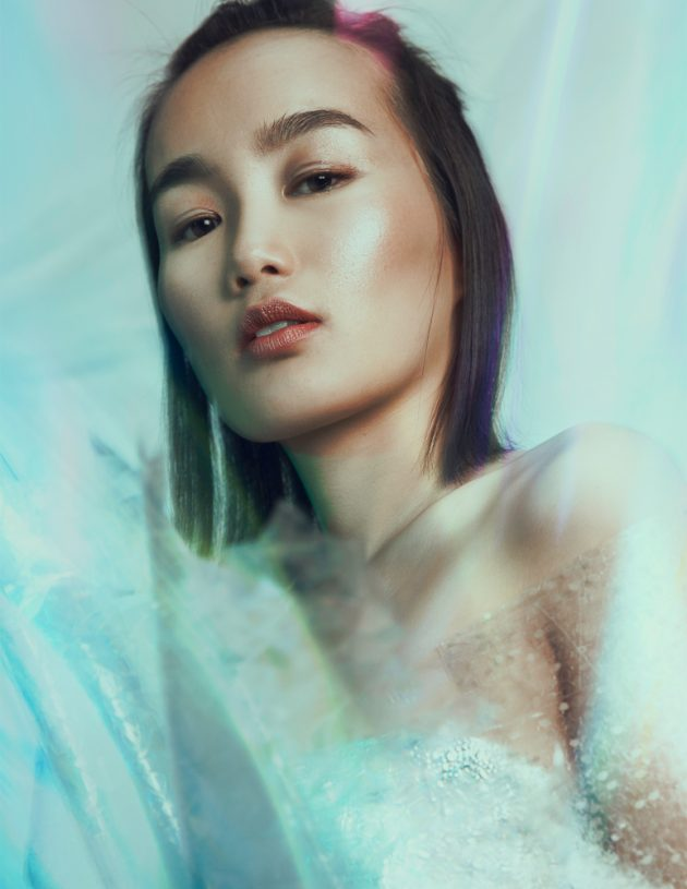 asian model wrapped in plastic on metallic backdrop