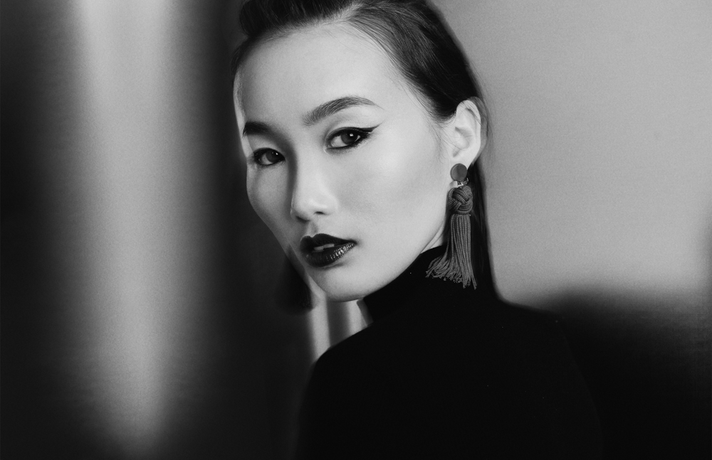 black and white closeup of asian model wearing blue lipstick and blue eyeliner on metal backdrop