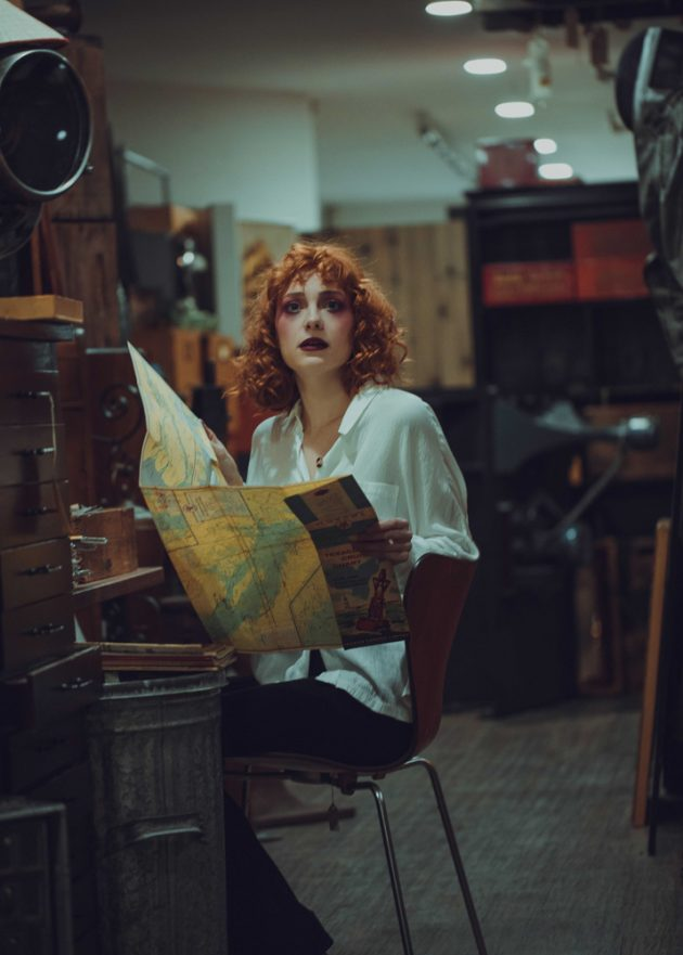 red hair girl sitting at old desk and holding old map in antiques store