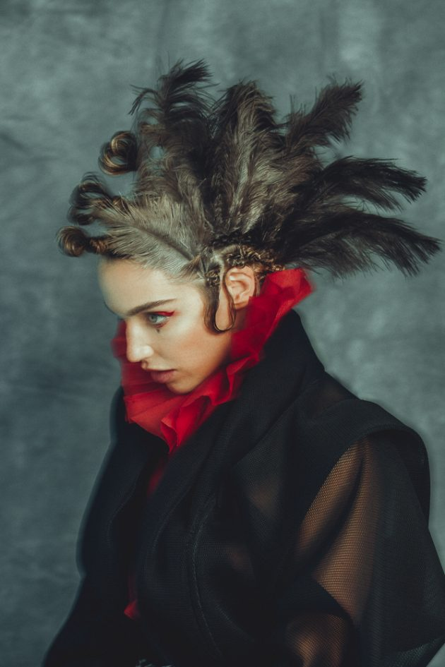 girl with extravagant hairstyle with feathers in her hair wearing black coat and red paper collar