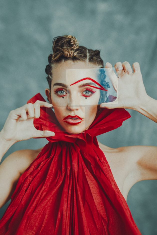 girl model wearing red eyeliner and red paper dress design looking through glass with extravagand hairstyle