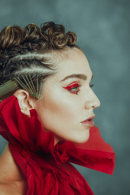 girl profile wearing red eyeliner and red paper dress design with extravagand hairstyle