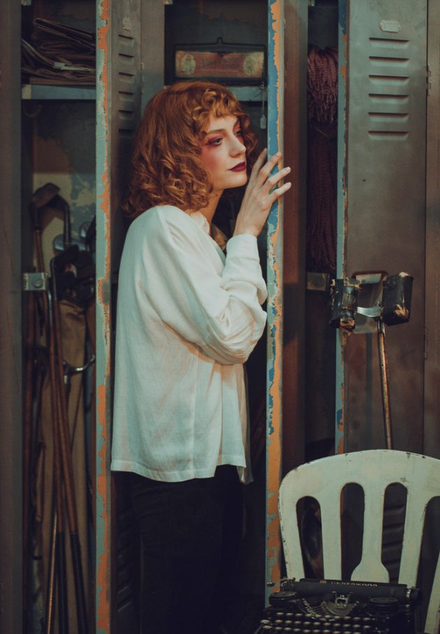 red hair girl laying against old drawer next to old lamp in antique store wearing white shirt