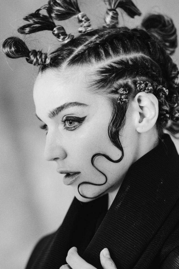 black and white profile of girl with extravagant hairstyle and red eyeliner on dark backdrop