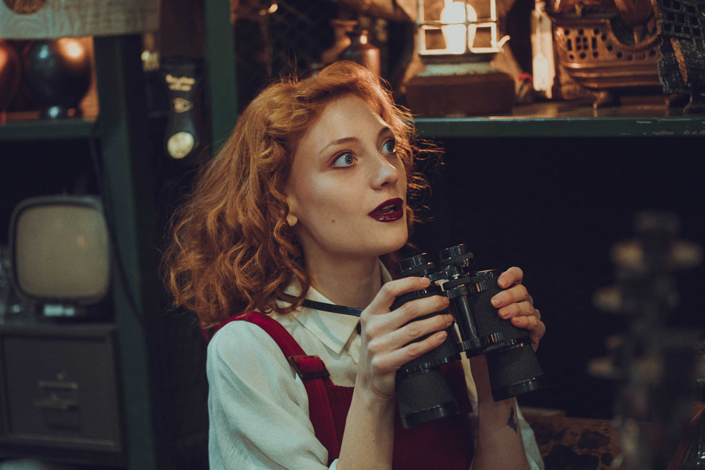 girl wearing red braces dress looking through binoculars in antiques store