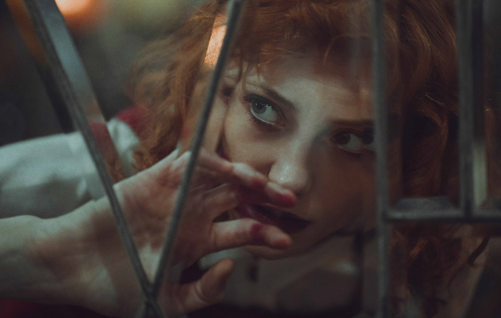 Cinematic image of girl looking through antique window glass