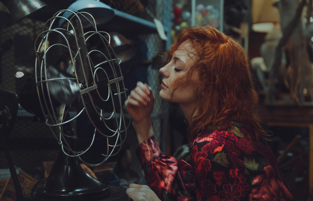 Girl using fan while wearing flowery red TopShop large dress in antiques store