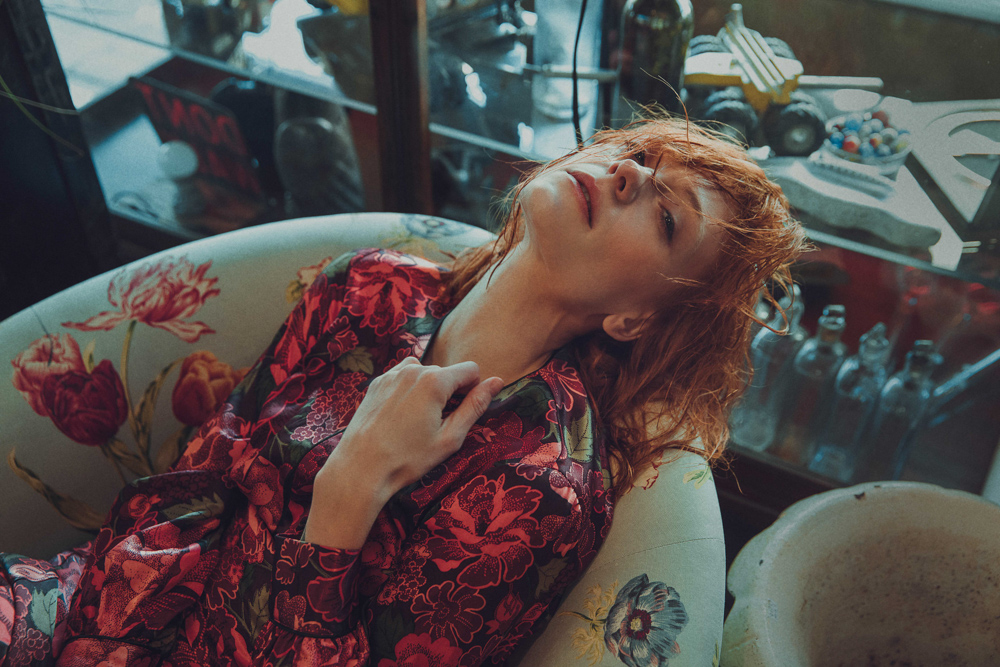 Girl laying on armchair while wearing flowery red TopShop large dress in antiques store