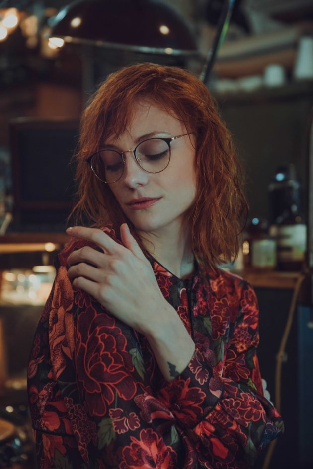 Girl looking straight while wearing flowery red TopShop large dress and TIJN glasses in antiques store