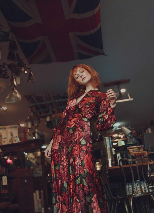 Girl dancing while wearing flowery red TopShop large dress under a US flag in antiques store