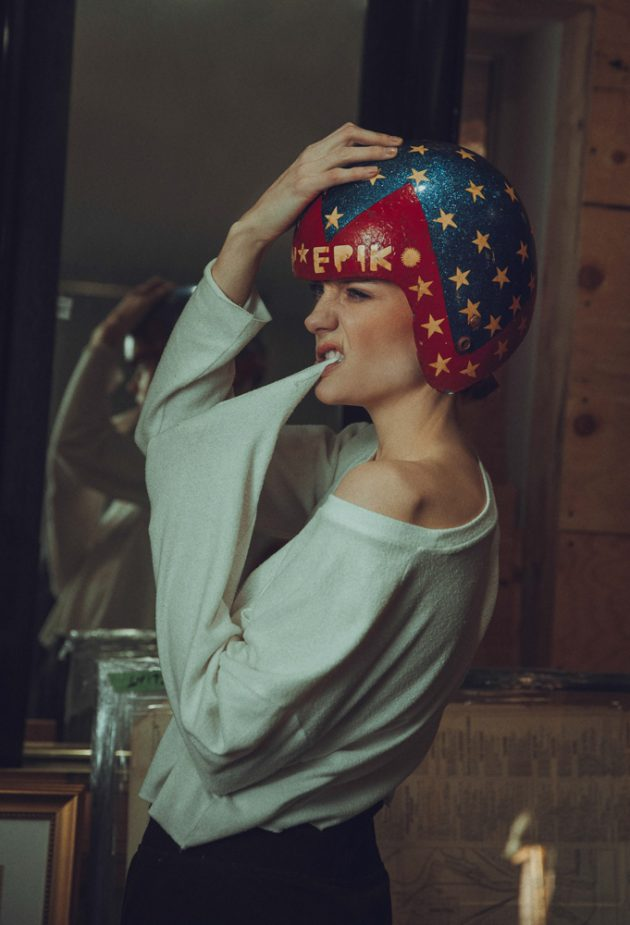 closeup of girl wearing old blue and red wooden helmet in antiques store