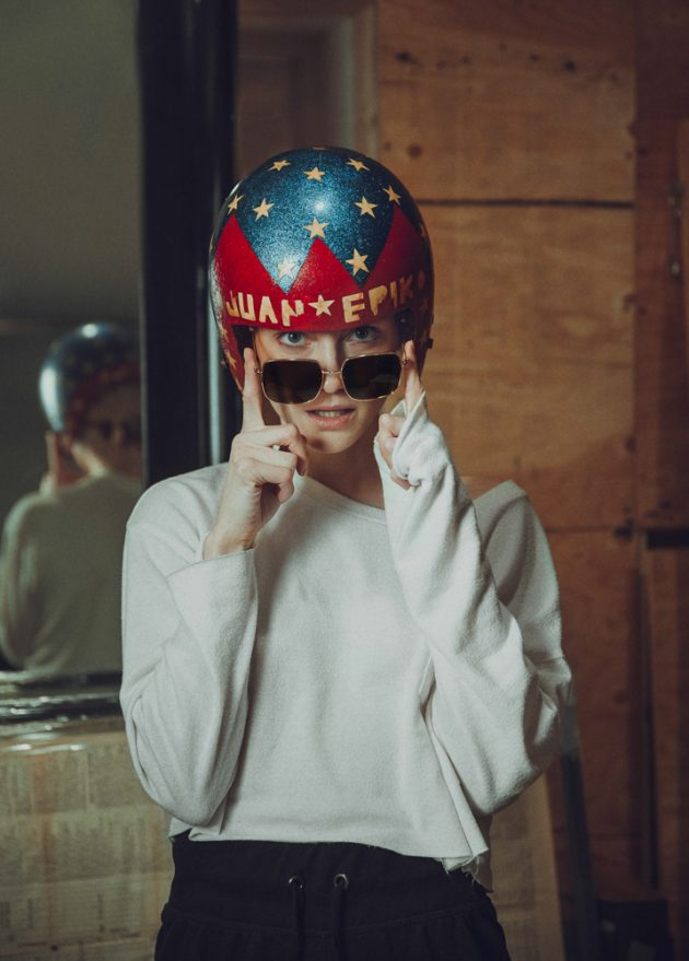 closeup of girl wearing old blue and red wooden helmet and TIJN sunglasses in antiques store