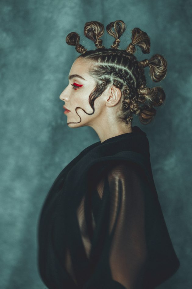 profile of girl with extravagant hairstyle and red eyeliner on dark backdrop