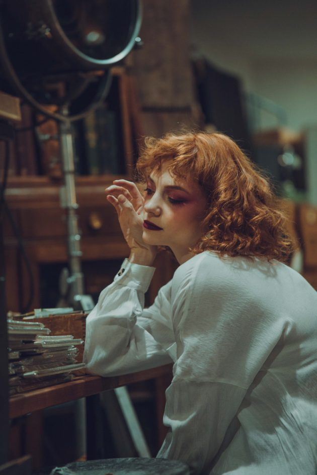 red hair girl sitting at old desk in antiques store