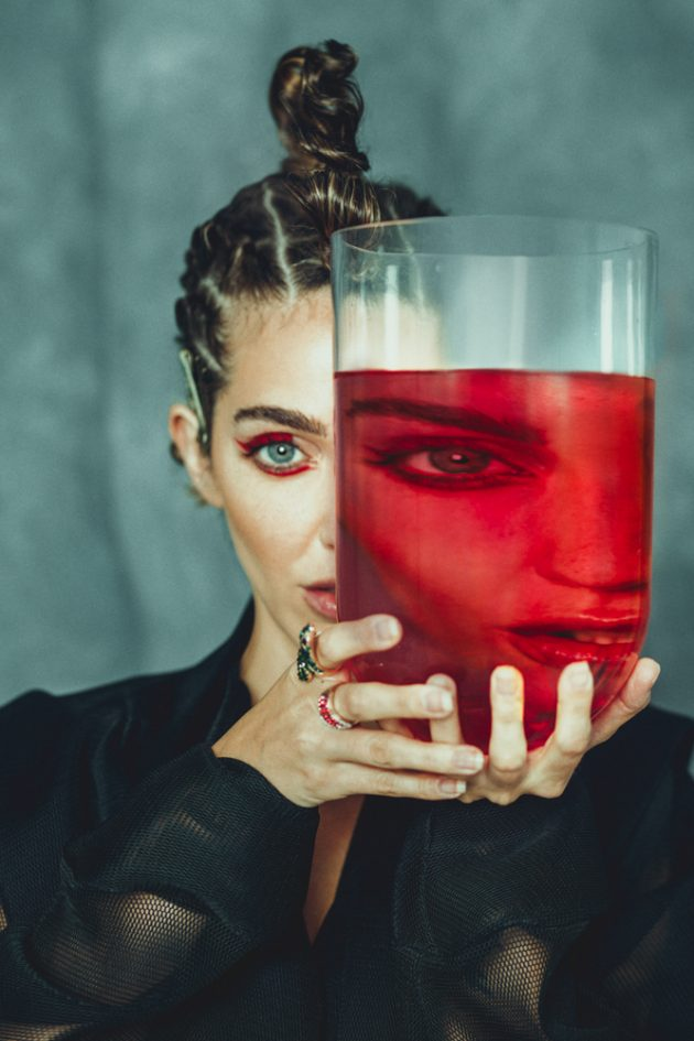 girl with extravagand hairstyle looking through red liquid