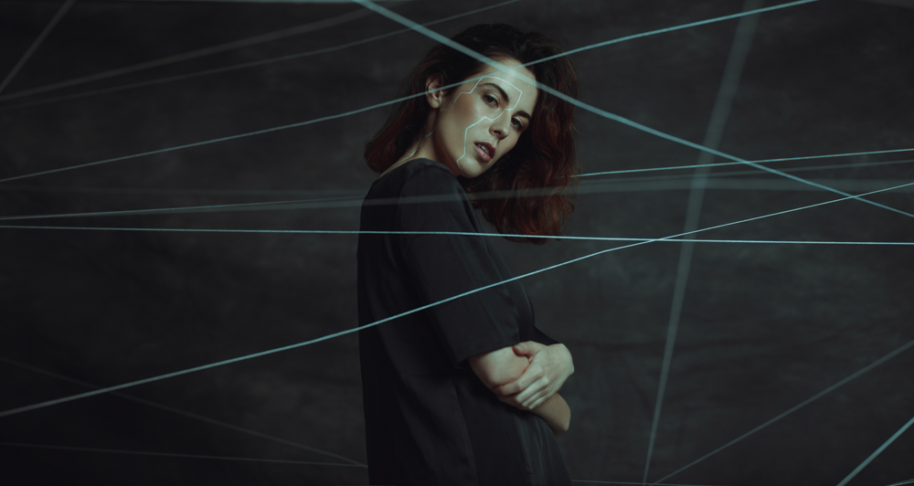 girl surrounded by white string acting like laser on dark backdrop